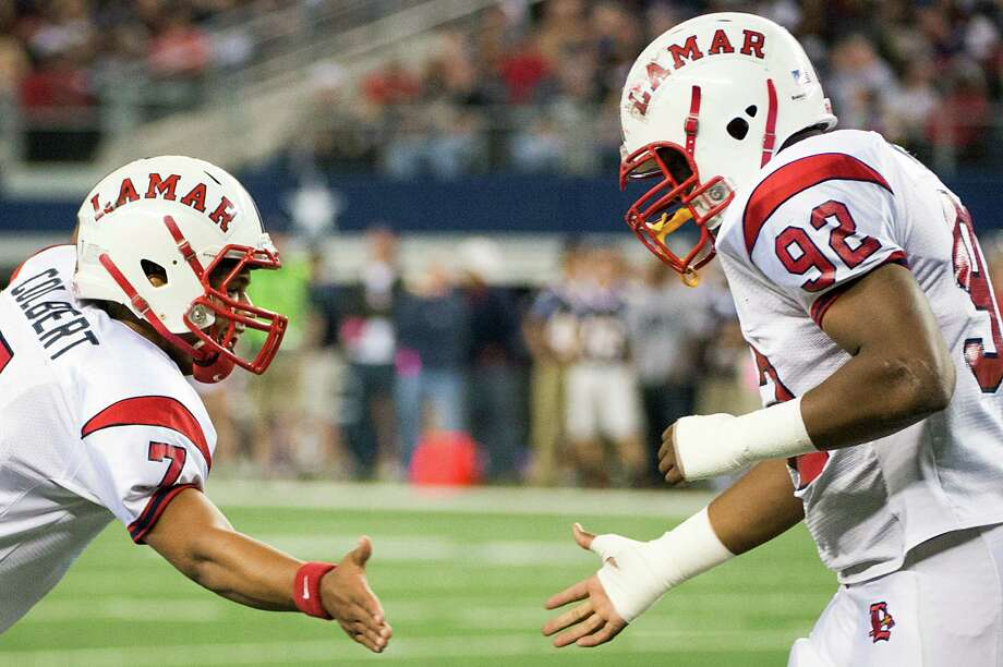 Lamar quarterback Darrell Colbert (7) celebrates with defensive lineman Zelt Minor (92) after a bad snap resulted in a safety against Allen during the first half of the Class 5A Division I state championship football game at Cowboys Stadium on Saturday, Dec. 22, 2012, in Arlington. Photo: Smiley N. Pool, Houston Chronicle / © 2012  Houston Chronicle
