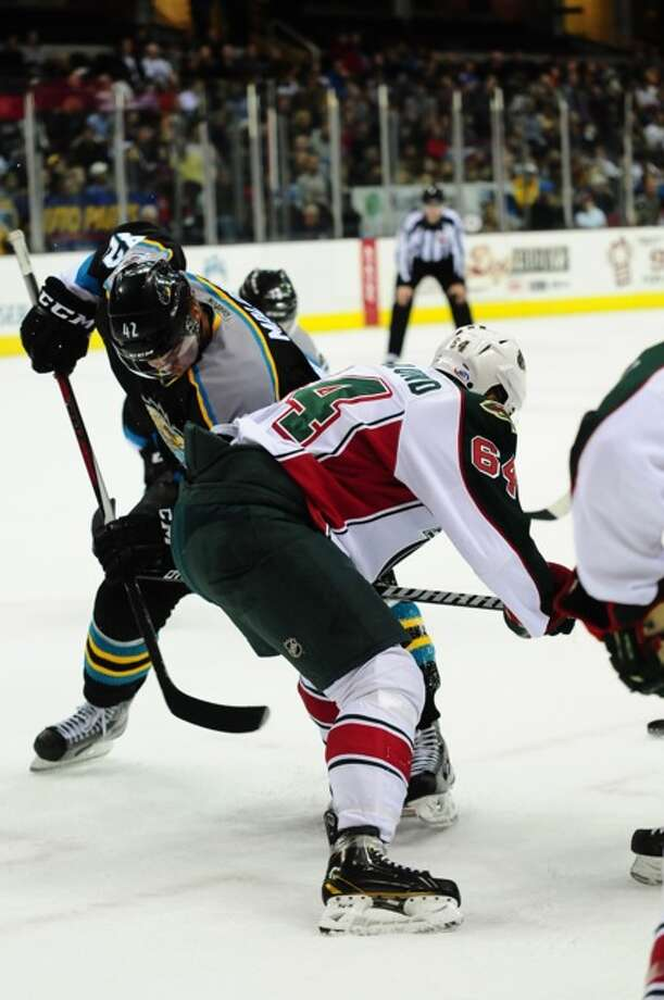 Monsters center Brad Malone (43) and Aeros center Mikael Granlund (64) fight for control of the puck.