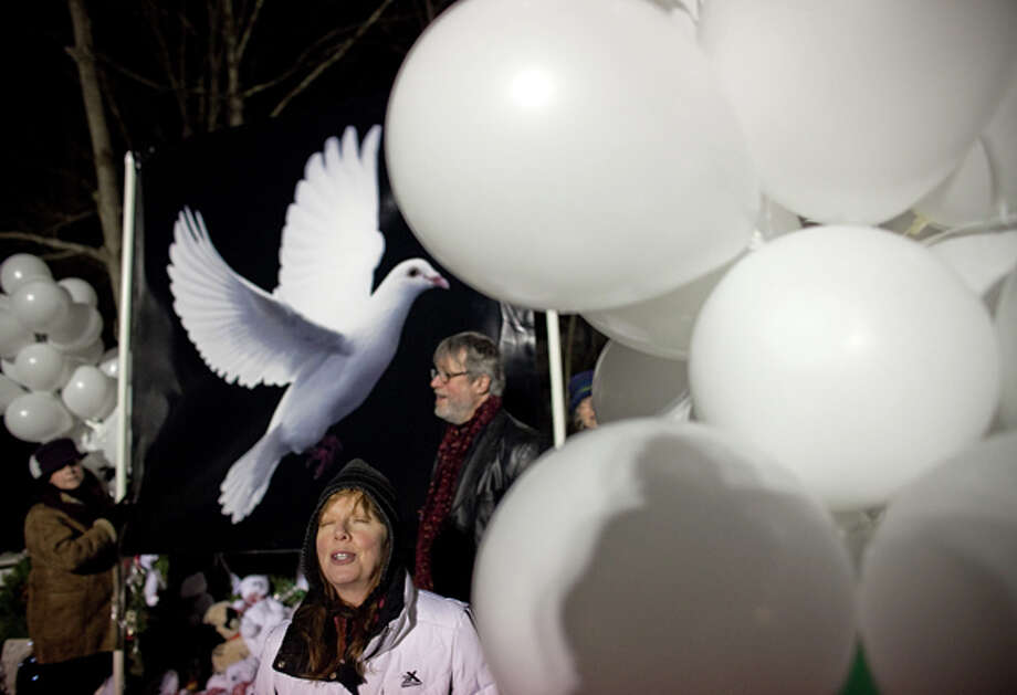 Newtown resident Veronica Marr sings a song about peace with other's during a evening peace march on Saturday, December 22, 2012 in Newtown. The group marched from Edmond Town Hall to Sandy Hook  and the growing memorial for the children and teachers killed up the road at Sandy Hook Elementary School. (Photo by Joshua Trujillo, Hearst Newspapers) Photo: Joshua Trujillo, Joshua Trujillo/Hearst Newspaper / News-Times
