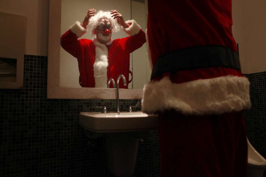Experimenting with a Santa suit for the holiday season, Kenneth Kahn transforms himself into Kenny the Clown in a public bathroom on Market Street  in San Francisco, Calif. (Mike Kepka / The Chronicle)
