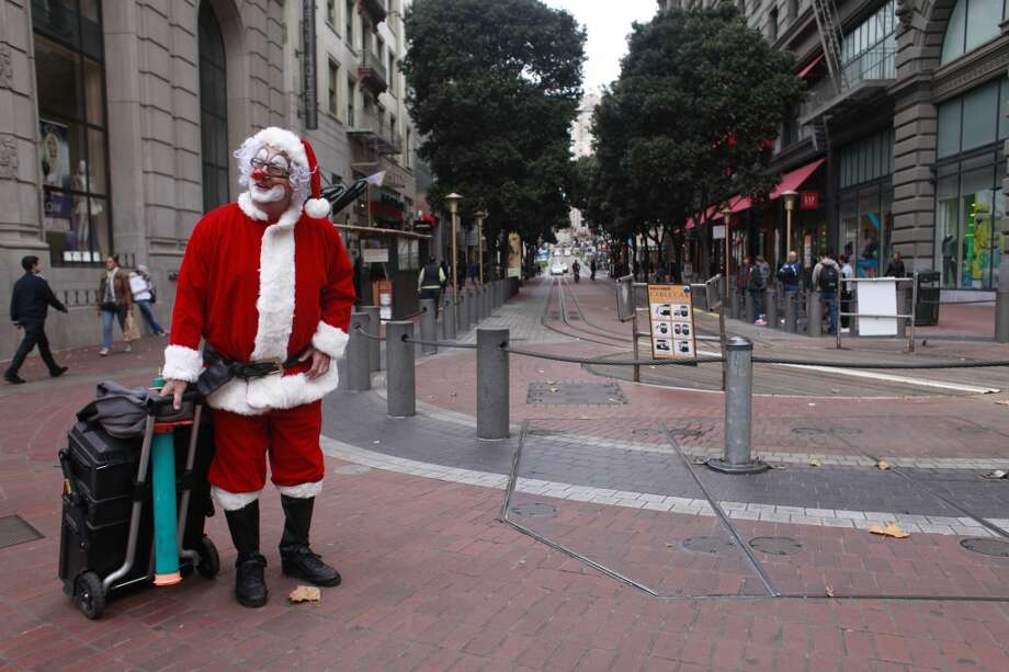 Thank you Santa, said street performer Kenny the Clown at he heads to Market Street in San Francisco, Calif. (Mike Kepka / The Chronicle)