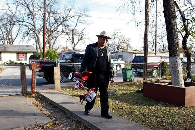 Juan Guajardo carries a tricycle for a two-year-old as he delivers presents to families in need with the Ghost Town Survivors in the neighborhood they grew up in on Thursday, Dec. 20, 2012. Photo: Lisa Krantz, San Antonio Express-News / © 2012 San Antonio Express-News