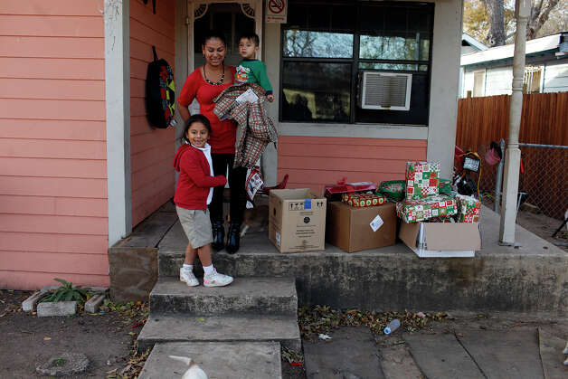 Estela Salas and her children Nahum Barrientos, 2, and Alma Barrientos, 6, watch as the group of Ghost Town Survivors leave their home after delivering boxes of presents, food and gift cards, right, to them on Thursday, Dec. 20, 2012 in San Antonio. Photo: Lisa Krantz, San Antonio Express-News / © 2012 San Antonio Express-News