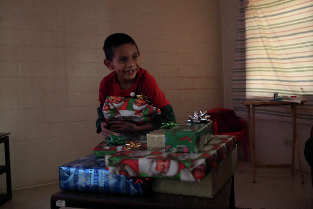 Sebastian Gonzalez, 7, tries to figure out what is beneath the wrapping paper in the presents given to him and his family by the Ghost Town Survivors at their apartment in Cassiano Homes on Thursday, Dec. 20, 2012. Photo: Lisa Krantz, San Antonio Express-News / © 2012 San Antonio Express-News