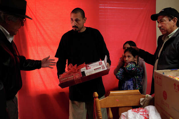 Single father Raymond Gonzalez, center, accepts presents including a gift basket of food with his daughters, Anastasia, 10, and Anna, 9, right, from the Ghost Town Survivors group including Luz H. Gallegos, left, and Hector Caldera, right, at their apartment in the Cassiano Homes complex on Thursday, Dec. 20, 2012 in San Antonio. Photo: Lisa Krantz, San Antonio Express-News / © 2012 San Antonio Express-News