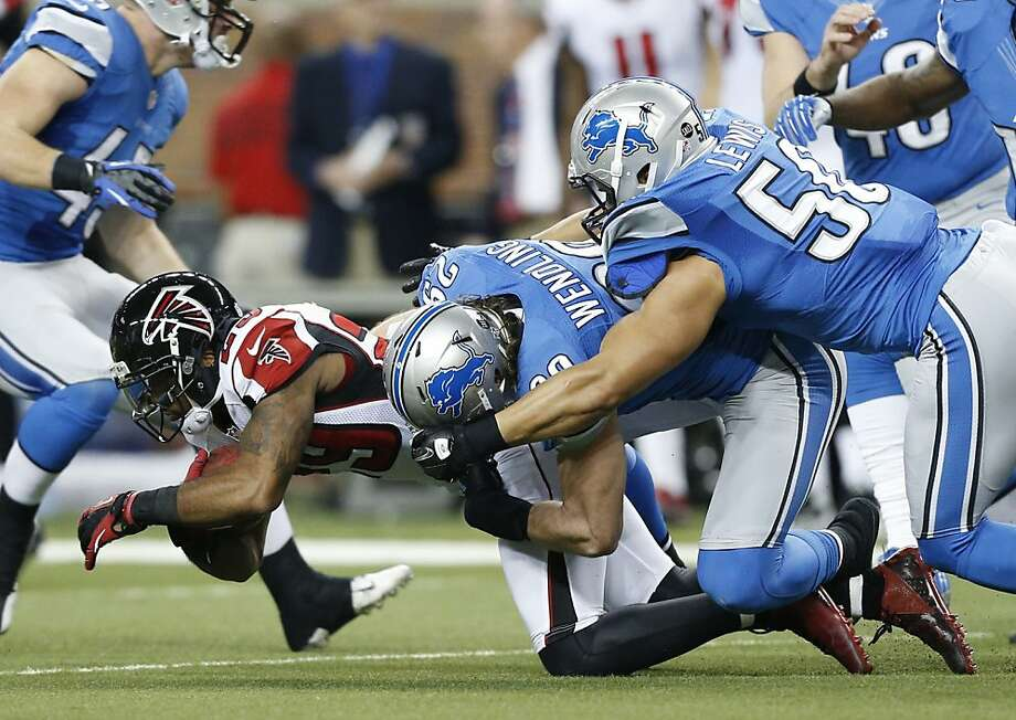 Atlanta Falcons defensive back Dominique Franks (29) is stopped by Detroit Lions free safety John Wendling (29) and linebacker Travis Lewis (50) during the first quarter of an NFL football game at Ford Field in Detroit, Saturday, Dec. 22, 2012. (AP Photo/Rick Osentoski) Photo: Rick Osentoski, Associated Press