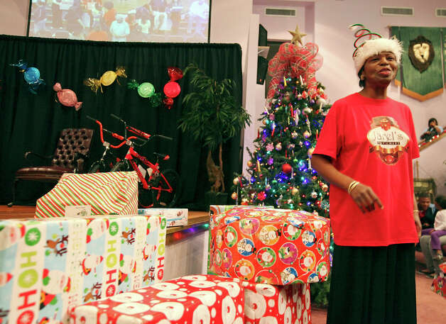 Deborah Melvin watches as children receive gifts during the Jarel's Toy Chest event held Saturday Dec. 22, 2012 at the New Life Christian Center.  Jarel's Toy Chest is named after her late son, Jarel, who enjoyed giving gifts to children. Photo: Edward A. Ornelas, San Antonio Express-News / © 2012 San Antonio Express-News