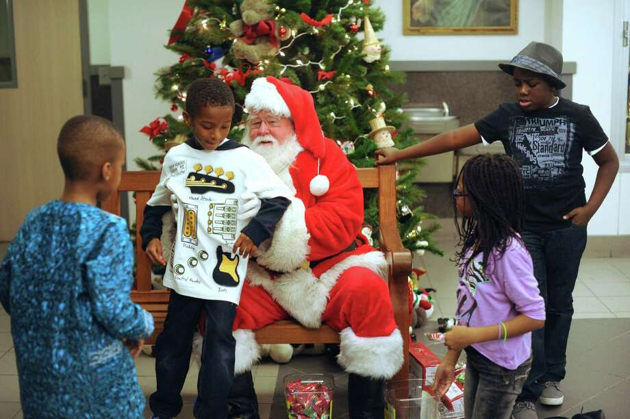 Children enjoy a moment with Santa Claus during the annual Christmas party for Nigerian children of San Antonio at St. Matthew Catholic Church on Saturday night, Dec. 22, 2012. Photo: Billy Calzada, San Antonio Express-News / SAN ANTONIO EXPRESS-NEWS