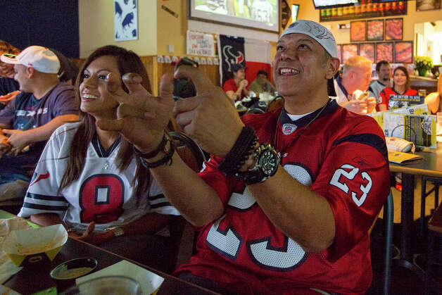 Oved Carranza of the Houston Texans Fan Club of San Antonio acts as if he is controlling game action through a video game during a Texans game against the Tennessee Titans at Buffalo Wild Wings Grill & Bar at 5860 De Zavala Road on Sunday, Dec. 2, 2012. Carranza has been a fan of the Texans since their first season in 2002. Photo: Michael Miller, For The Express-News / © San Antonio Express-News