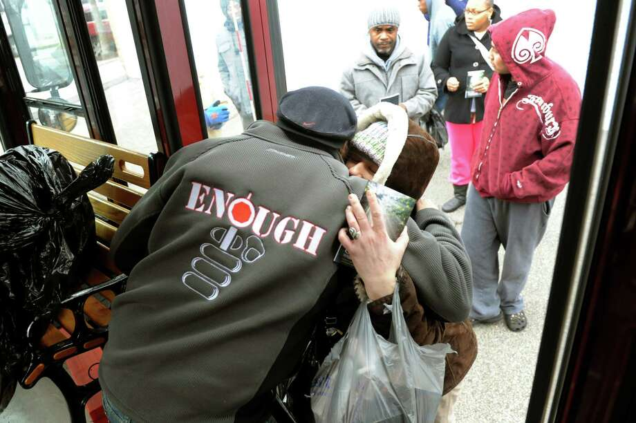 A woman, who identified herself as Susie, hugs Pastor Charlie Muller when she receives a bag of toys for her three children during a Christmas Toy Giveaway on Saturday, Dec. 22, 2012, outside the Victory Church in Albany, N.Y. Susie said that she's out of work and the gifts for her children mean everything to her. (Cindy Schultz / Times Union) Photo: Cindy Schultz / 00020564A