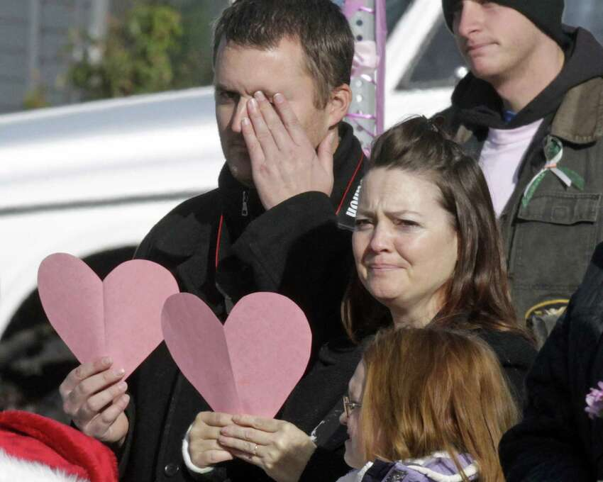 Mourners line the street as a hurst carrying Emilie Parker drives by following funeral services for the 6-year old Connecticut elementary shooting victim, Saturday, Dec. 22, 2012, in Ogden, Utah.  Emilie, whose family has Ogden roots, was one of 20 children and six adult victims killed in a Dec. 14 mass shooting at Sandy Hook Elementary in Newtown, Conn. Photo: Rick Bowmer, (AP Photo/Rick Bowmer) / Associated Press