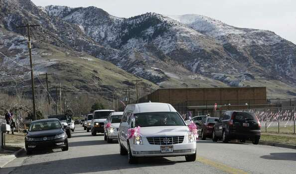A hearse carrying the casket Emilie Parker drives along the street following funeral services on Saturday, Dec. 22, 2012, in Ogden, Utah. Emilie, 6, whose family has Ogden roots, was one of 20 children and six adult victims killed in a Dec. 14 mass shooting at Sandy Hook Elementary in Newtown, Conn. Photo: Rick Bowmer, (AP Photo/Rick Bowmer) / Associated Press
