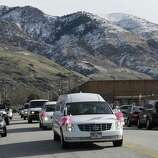 A hearse carrying the casket Emilie Parker drives along the street following funeral services on Saturday, Dec. 22, 2012, in Ogden, Utah. Emilie, 6, whose family has Ogden roots, was one of 20 children and six adult victims killed in a Dec. 14 mass shooting at Sandy Hook Elementary in Newtown, Conn.