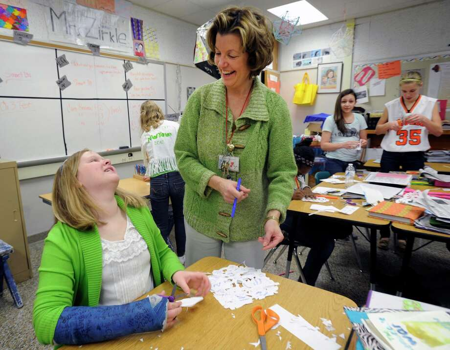 Suburban Middle School 8th grader Jillian Ducker, talks to her teacher Peggy Zirkle,  creates snowflakes to send to Newtown to help with the healing process,  Friday, Dec. 21, 2012 in York, Pa.. Photo: Jason Plotkin, AP Photo/York Daily Record, Jason Plotkin / Associated Press