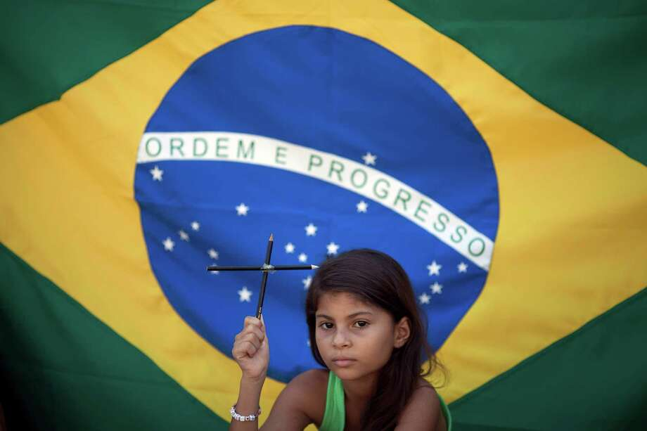 Larissa Vitoria, 7, who lives across the street from the Tasso da Silveira school where 12 children were killed by a gunman in April 2011, holds a cross made of pencils during a demonstration to protest violence in schools in the Realengo neighborhood of Rio de Janeiro, Brazil, Friday, Dec. 21, 2012. Family members and neighbors of the victims held the protest in light of the recent school shooting in Newtown, Conn.  A Brazilian flag hangs behind her. Photo: Felipe Dana, AP Photo/Felipe Dana / Associated Press