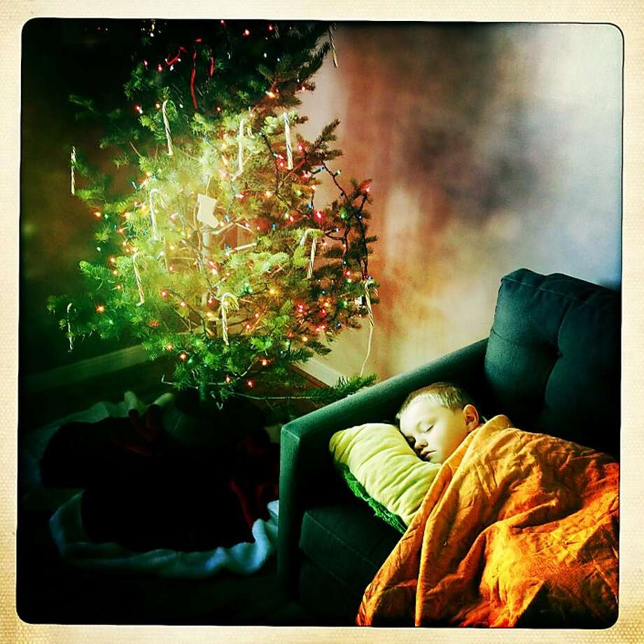 Theo DeHaas camps out on the sofa waiting for Santa's appearance. Photo: Judy Walgren, The Chronicle