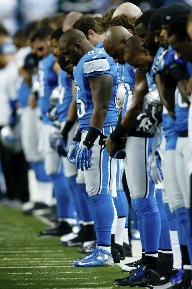 Detroit Lions middle linebacker Stephen Tulloch (55) and his teammates bow their heads in a moment of silence for Sandy Hook Elementary school before an NFL football game against the Atlanta Falcons at Ford Field in Detroit, Saturday, Dec. 22, 2012. Photo: Rick Osentoski, (AP Photo/Rick Osentoski) / Associated Press