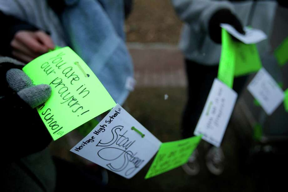 Notes from Heritage High School in Leesburg, Va. are placed at a memorial to the Newtown shooting victims in the Sandy Hook village of Newtown, Conn., Saturday, Dec. 22, 2012.   The funerals for the victims of the school shooting are wrapping up after a wrenching week of farewells. Twenty children and six adults were killed at Sandy Hook Elementary School on Dec. 14.  Adam Lanza, the lone gunman, killed his mother before going on the rampage and then committed suicide. Photo: Seth Wenig, (AP Photo/Seth Wenig) / Associated Press