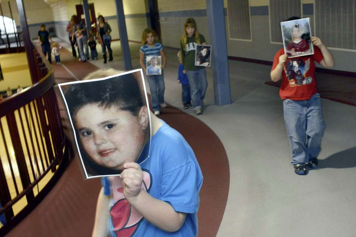Holding photos of shooting victims from the December 14 tragedy at Sandy Hook Elementary School in Newton, Conn., participants in a memorial walk circle the track at the Wabash County YMCA for 27 minutes Friday, Dec. 21, 2012, in Wabash, Ind.