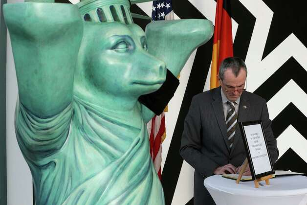 US Ambassador in Germany, Philip D. Murphy, writes in a condolence book in Berlin, Germany, Monday, Dec. 17, 2012, for the death of the children and teachers of the Sandy Hook elementary school in Newtown. Photo: Michael Sohn, (AP Photo/Michael Sohn) / Associated Press