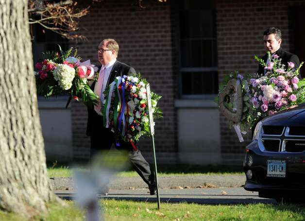 Flowers are carried away from the church after a funeral service for shooting victim Charlotte Bacon, held at Christ the King Lutheran Church in Newtown, Conn. Wednesday, Dec. 19, 2012. Photo: Carol Kaliff / The News-Times