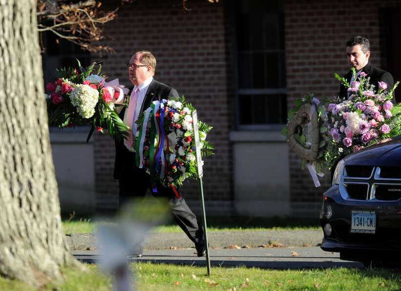 Flowers are carried away from the church after a funeral service for shooting victim Charlotte Bacon