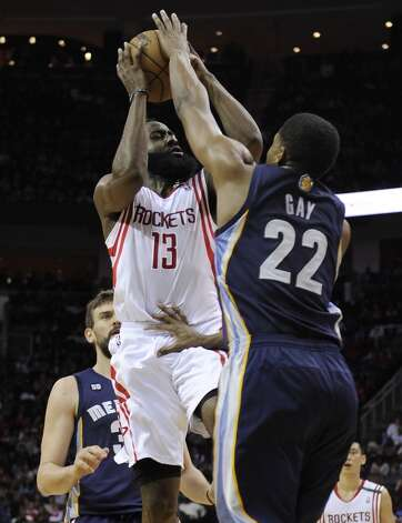 Rockets guard James Harden tries to shoot while guarded by Rudy Gay and Marc Gasol of the Grizzlies. (Pat Sullivan / Associated Press)
