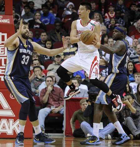Rockets guard Jeremy Lin looks to pass the ball between Grizzlies defenders Marc Gasol and Zach Randolph. (Pat Sullivan / Associated Press)