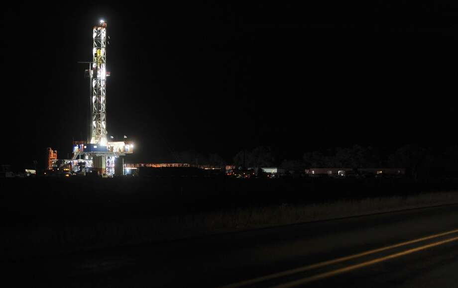 A hydraulic fracturing drilling rig shines in the night near Three Rivers, Texas, on Thursday, Dec. 13, 2012. (San Antonio Express-News)
