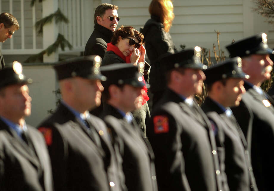 A bystander wipes a tear as firefighters stand at attention outside the funeral for Daniel Barden, one of the twenty children killed in the Sandy Hook Elementary School shooting, at St. Rose of Lima Catholic Church in Newtown on Wednesday, December 19, 2012. Photo: Brian A. Pounds / Connecticut Post