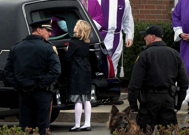 A little girl looks into the hearse carrying the casket of Josephine Gay after her funeral at St. Rose of Lima Roman Catholic Church, Saturday, Dec. 22, 2012, in Newtown. Soll was one of 26 killed after gunman Adam Lanza opened fire killing 26 individuals, 20 whom were children, at Sandy Hook Elementary School last Friday. Photo: Cody Duty, Cody Duty/Hearst Newspapers / The News-Times
