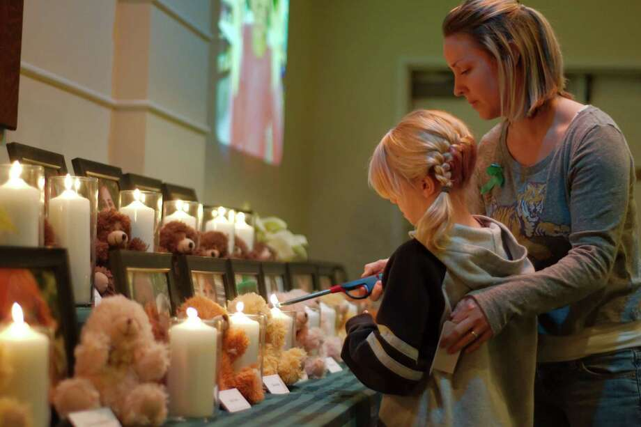 Betsy S. Willson and her daughter Savannah R. Robinson light a candle for Josephine Gay during a vigil in Pearland, Texas Friday, Dec. 21, 2012. Photo: Kirk Sides, (AP Photo/The Courier, Kirk Sides) / Associated Press