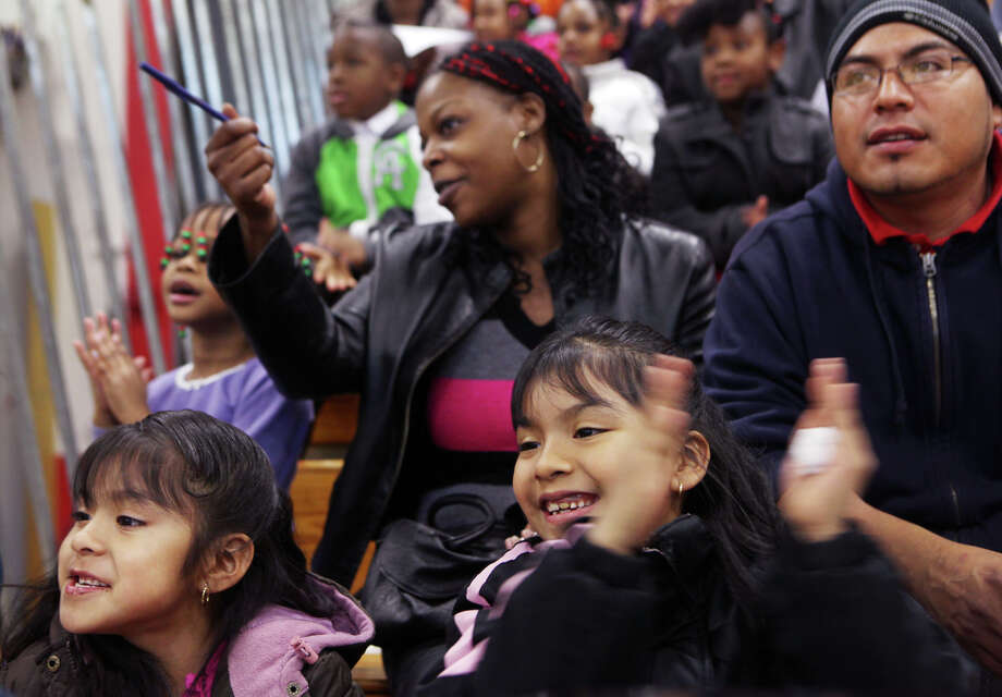 Yaritza Aca, 6, right, cheers before the Bridgeport , Conn. Police Department bicycle give away at Central High School on Sunday, December 23, 2012. The PD raised money to give 300 city children bikes and helmets. Photo: Unknown, B.K. Angeletti / Connecticut Post freelance B.K. Angeletti