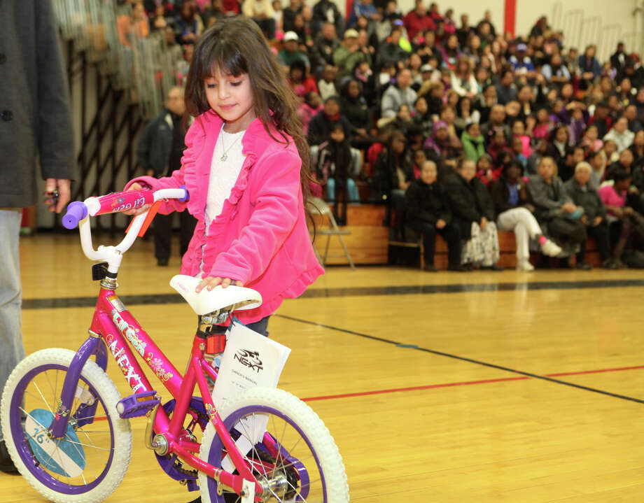 Mia Gonzales, 6, picks up her new bicycle. Photo: Unknown, B.K. Angeletti / Connecticut Post freelance B.K. Angeletti
