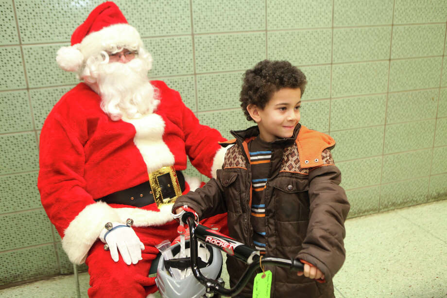 Jayquan Shipman, 6, has his picture taken with Santa, Benji Labader, and his new bicycle. Photo: Unknown, B.K. Angeletti / Connecticut Post freelance B.K. Angeletti