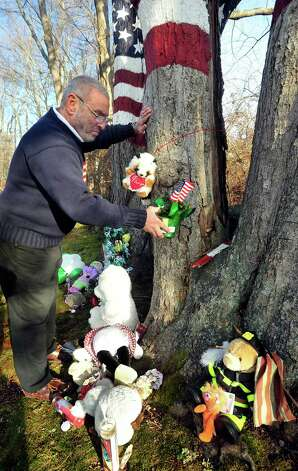 Howard Lasher places a flag at a monument to those lost at the Sandy Hook Elementary School shooting. The 9-11 memorial maple trees in his yard along Route 302 are familiar to area residents. He says outgoing support from the Newtown community has been overwhelming. Photographed Sunday, Dec. 23, 2012. Photo: Michael Duffy