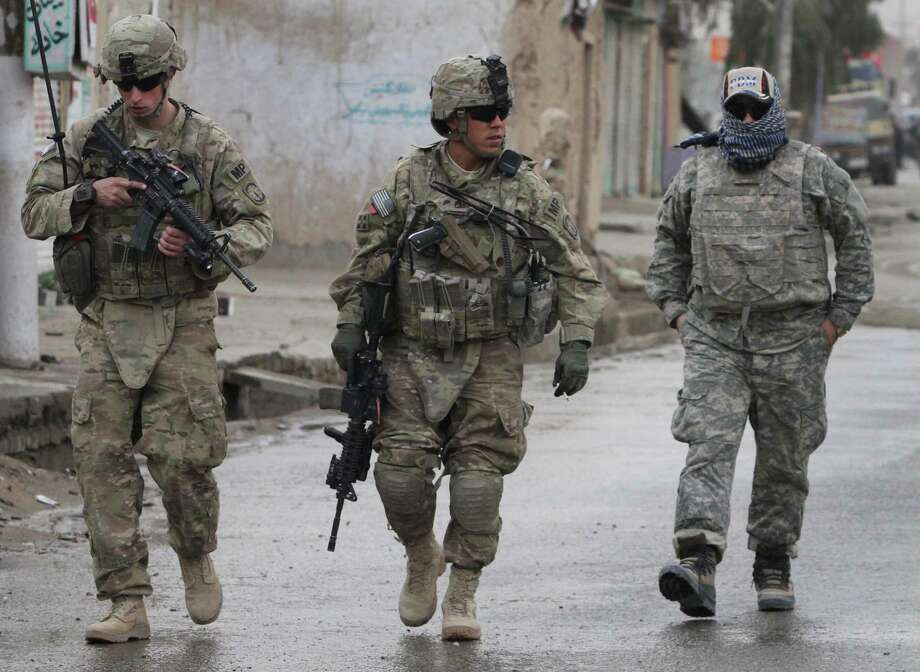 U.S. soldiers walk with their Afghan translator in Kandahar. Soon, U.S. troops will be going home, but the State Department is blocking visas for  Afghans who made it possible for  Americans to do their job. Photo: Allauddin Khan, Associated Press / AP