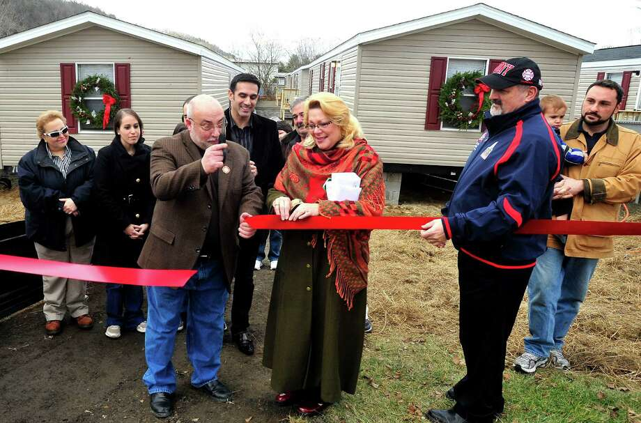 New Fairfield First Selectman John Hodge, left center, Faith Church Senior Pastor Frank Santora, center, and New Milford Mayor Pat Murphy, join Staten Island families in a ribbon-cutting ceremony as they move into new homes on Faith Church property in New Milford Sunday, Dec. 23, 2012. Photo: Michael Duffy / The News-Times