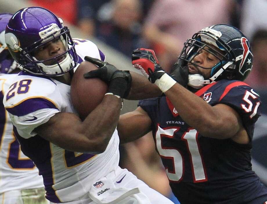 Texans linebacker Tim Dobbins tries to bring down Vikings running back Adrian Peterson. (Karen Warren / Houston Chronicle)