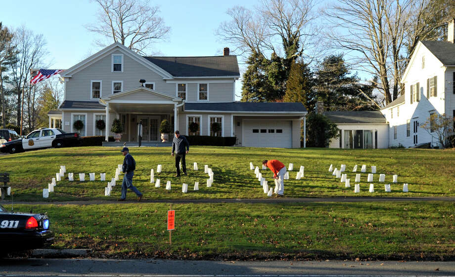 People adjust the luminaries on the front lawn of the Munson Lovetere funeral home durng the funeral services of Sandy Hook principal Dawn Lafferty Hochsprung in Woodbury on Wednesday, Dec. 19, 2012. Photo: Jason Rearick / The News-Times