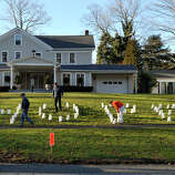 People adjust the luminaries on the front lawn of the Munson Lovetere funeral home durng the funeral services of Sandy Hook principal Dawn Lafferty Hochsprung in Woodbury on Wednesday, Dec. 19, 2012.