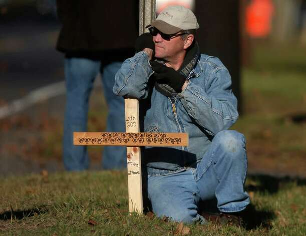 A mourner kneels with a cross marked with 26 angels across from the calling hours for Sandy Hook Elementary School principal Dawn Lafferty Hochsprung, Wednesday, Dec. 19, 2012, in Woodbury, Conn.  Hochsprung was killed when a gunman forced his way into Sandy Hook Elementary School in Newtown on Dec. 14 and opened fire, killing 26 people, including 20 children. (AP Photo/Jason DeCrow) Photo: Jason DeCrow / Associated Press