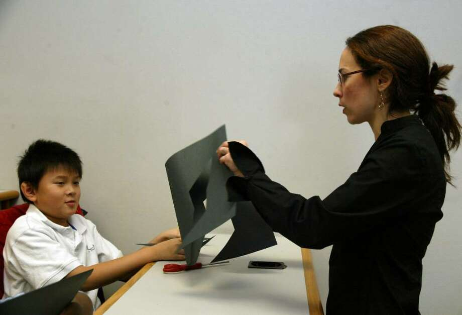 Professor Jennifer Goldberg of Fairfield University shows, Bridgeport Blackham School, 4th grade student, Danny Mai how math relates to art, using a construction paper cutout, at the University. Monday, Dec. 21, 2009.2 Photo: Phil Noel / Connecticut Post
