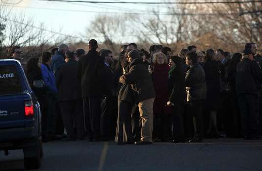 Mourners hug outside the wake of school principal Dawn Hochsprung, December 19, 2012 in Woodbury, Connecticut. Six victims of the Newtown school shooting are being honored at funerals and visitations across the state today for the victims of Sandy Hook Elementary School. (Photo by Allison Joyce/Getty Images) Photo: Allison Joyce, (Photo By Allison Joyce/Getty Images) / 2012 Getty Images