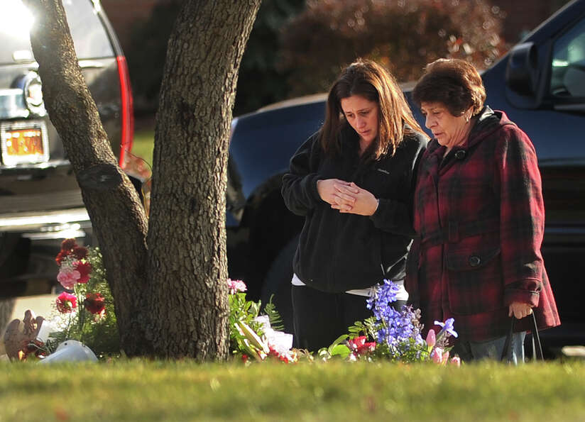 Mourners visit a memorial outside St. Rose of Lima Catholic Church, site of the funeral of Catherine
