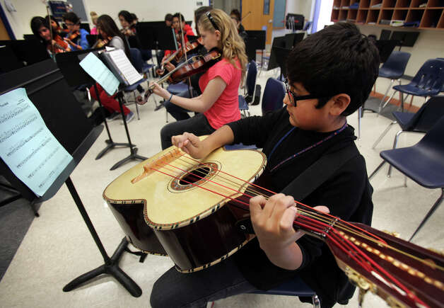 Seventh-grader Mario Morado, 12, plays the guitarrón in Angela Campos' mariachi class at Wood Middle School. Photo: Bob Owen, San Antonio Express-News / © 2012 San Antonio Express-News