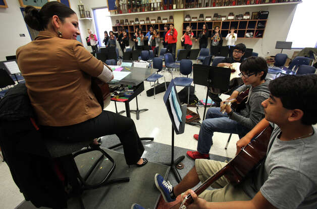 Angela Campos, left, Orchestra and Mariachi teacher at Wood Middle School in North East ISD, listens to the guitar section during class. Tuesday, Dec. 11, 2012. Photo: Bob Owen, San Antonio Express-News / © 2012 San Antonio Express-News