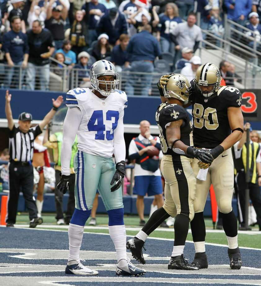 Dallas Cowboys free safety Gerald Sensabaugh (43) stands in the end zone as New Orleans Saints running back Pierre Thomas (23) celebrates his touchdown with teammate Jimmy Graham (80) during the second half of an NFL football game Sunday, Dec. 23, 2012 in Arlington, Texas.(AP Photo/Sharon Ellman) Photo: Sharon Ellman, Associated Press / AP