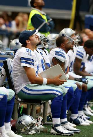 Dallas Cowboys quarterback Tony Romo (9) looks up from the bench with teammates during the second half of an NFL football game against the New Orleans Saints Sunday, Dec. 23, 2012 in Arlington, Texas. (AP Photo/Sharon Ellman) Photo: Sharon Ellman, Associated Press / FR170032 AP