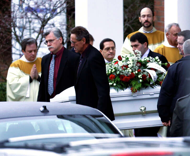 Pallbearers carry a casket out of St. Rose of Lima Roman Catholic Church after funeral services for